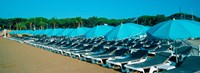"Parasols with lounge chairs on a private beach in summer morning light, French Riviera, France by Panoramic Images - 25"" x 9"""
