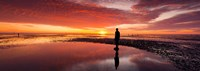 """Silhouette of human sculpture on the beach at sunset, Another Place, Crosby Beach, Merseyside, England by Panoramic Images - 34"""" x 12"""""""