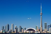 Airplane over city skylines, CN Tower, Toronto, Ontario, Canada 2011 Framed Print