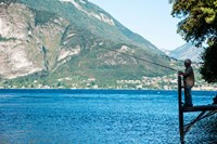 Man Fishing from Dock on Edge of Lake Como, Varenna, Lombardy, Italy Fine Art Print