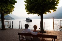 Couple sitting on bench and watching ferry approaching dock along the Lake Como, Bellagio, Province of Como, Lombardy, Italy Fine Art Print