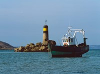 Fishing trawler in front of a lighthouse at Port Saint-Sauveur, Ile Grande, Cotes-d'Armor, Brittany, France by Panoramic Images - various sizes