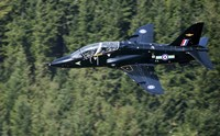 A Hawk T1 trainer aircraft of the Royal Air Force flying over a forest in North Wales Fine Art Print