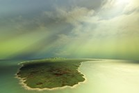 Beautiful rays of sun stream down on an island in the ocean by Corey Ford - various sizes