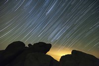 Light pollution illuminates the sky and star tails above large boulders Fine Art Print