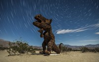 Tyrannosaurus rex sculpture against a backdrop of star trails, California by Dan Barr - various sizes