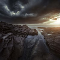 Huge rocks on the shore of a sea against stormy clouds, Sardinia, Italy Fine Art Print