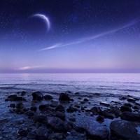 Moon rising over rocky seaside against starry sky Fine Art Print