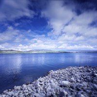 Tranquil lake and rocky shore against cloudy sky, Sardinia, Italy by Evgeny Kuklev - various sizes