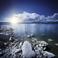 Tranquil lake and rocky shore with sun over horizon, Sardinia, Italy by Evgeny Kuklev - various sizes