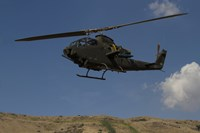 An AH-1F Tzefa of the Israeli Air Force flying over the Golan Heights, Israel Fine Art Print