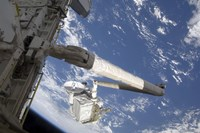 The Integrated Cargo Carrier in the grasp of the shuttle's remote manipulator system arm - various sizes