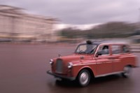 Cab racing past Buckingham Palace, London, England Fine Art Print