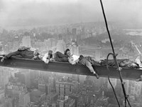Construction Workers Resting on Steel Beam Above Manhattan, 1932 Framed Print