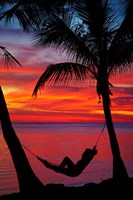 Woman in hammock, and palm trees at sunset, Fiji Fine Art Print