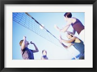 Low angle view of two young couples playing beach volleyball Fine Art Print