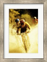 Young men riding bicycles through water Fine Art Print