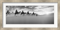 Tourists riding camels through the Sahara Desert landscape led by a Berber man, Morocco (black and white) Fine Art Print