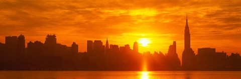 Birght Orange Sky and Sun Behind the New York City Skyline by Panoramic Images