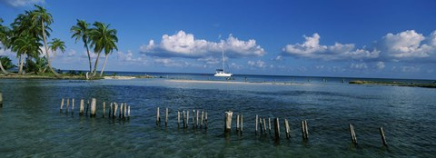 Framed Wooden posts in the sea with a boat in background, Laughing Bird Caye, Victoria Channel, Belize Print