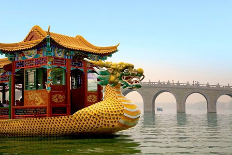 Framed Summer Palace, a traditional Dragon Boat passes the Seventeen Arch Bridge, Kunming lake, Beijing, China Print