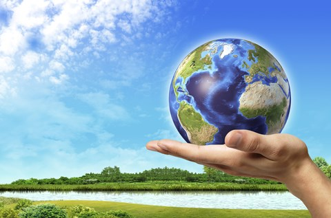 Framed Human Hand Holding Earth Globe with a Green Landscape Background Print