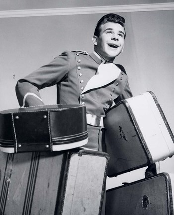 Framed 1950s Smiling Bellboy Carrying Four Bags Of Luggage Print